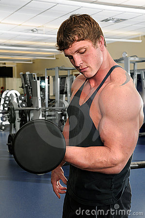 Man Curling Dumbbell at Gym