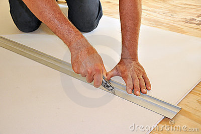 Man cutting drywall with utility knife