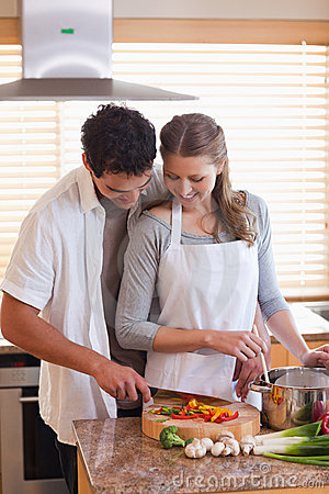 Man cutting ingredients to help his girlfriend