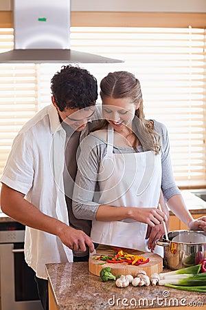 Man cutting ingredients to help his girlfriend