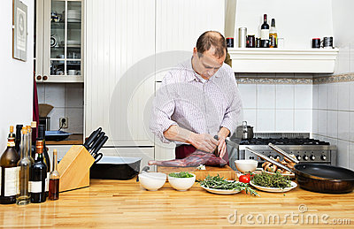 Man Cutting Meat On Chopping Board