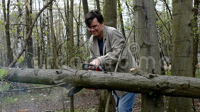 Man cutting wood by chainsaw stock video