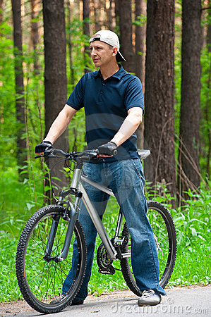 Man with cycle in park