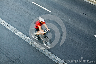 Man cycling on city street, motion