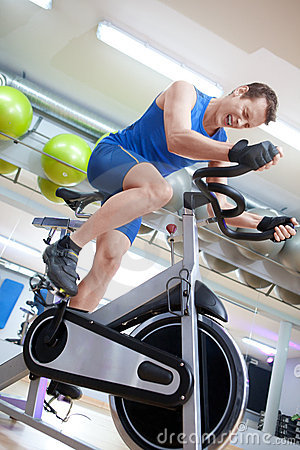 Free Man Cycling On Spinning Bike With Great Effort Stock Images - 17816624