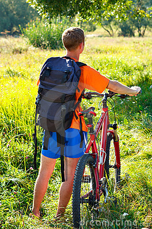 Man cyclist with bike and backpack