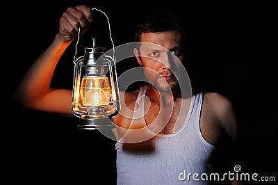 Man in the dark with a kerosene lamp