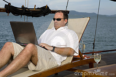 Man on deck of yacht with laptop