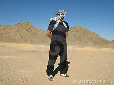 Man in desert with keffiyeh