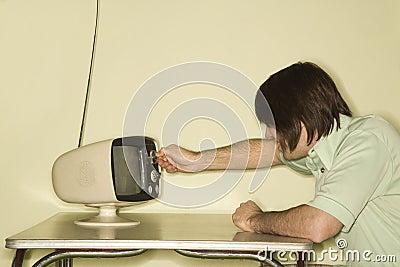 Man dialing television knob.