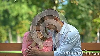 Man die huilende vrouw in het park omhelst en steunt, relatieve dood, saamhorigheid stock video