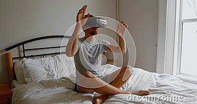 Man die virtuele reality-headset gebruikt op bed in slaapkamer 4.000 stock footage