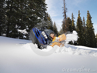 Man digging out snowmobile.
