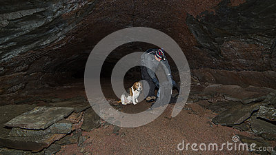 A man and a dog in a cave.