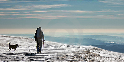 Man and dog climbing mountains