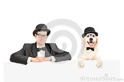 Man and dog with hats posing behind panel