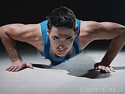 Man doing push-ups on black background