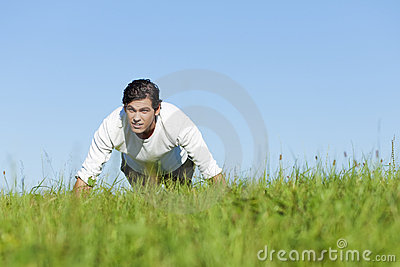 Man doing push ups in summer grass