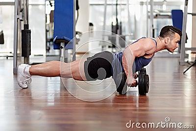 Man doing pushups on dumbbells