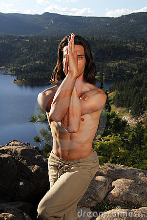 Man doing yoga on a mountain top