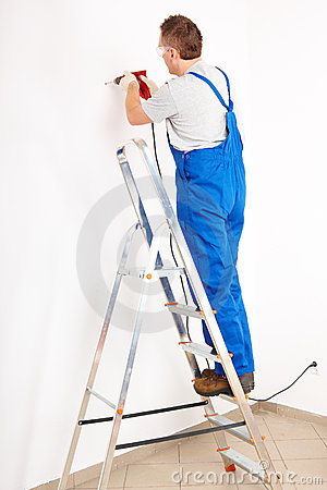 Man drilling hole standing on ladder