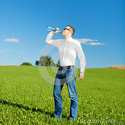 Man drinking bottled water in a field
