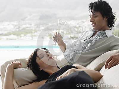 Man Drinking Champagne With Woman Lying On His Lap