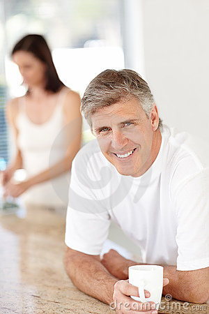 Man drinking coffee with his wife standing at back