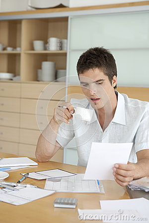 Man Drinking Coffee and Working on Finances