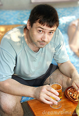 Man drinking lager beer with nuts
