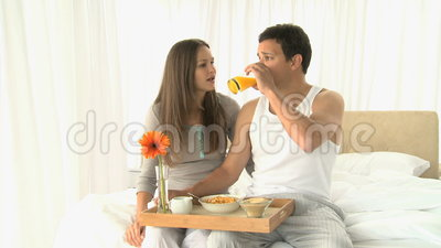 Man drinking orange juice while he having breakfast with his wife Stock Photo