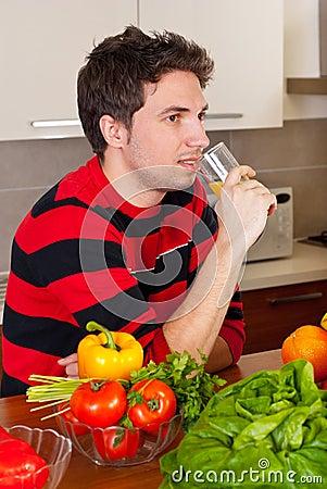 Man drinking orange juice in kitchen