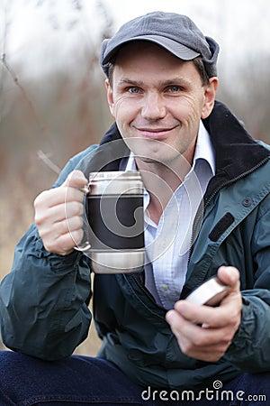 Man drinking tea outdoors