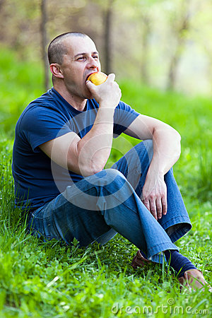 Man eating an apple outdoor