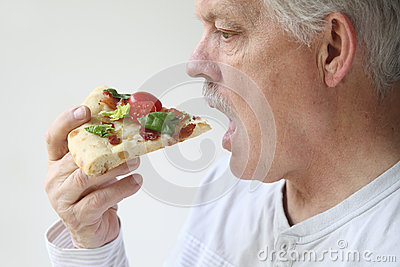 Man eats BLT pizza profile view