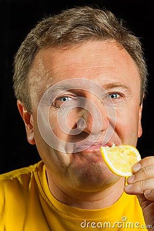 A man eats a lemon