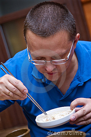 Free Man Eats With Chopsticks Royalty Free Stock Photo - 15250285