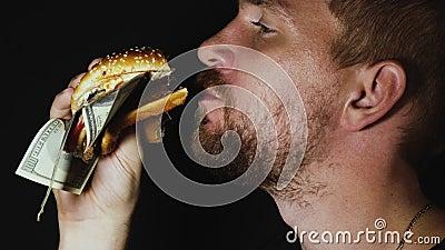 Man eet hamburger met Amerikaanse dollars stock video