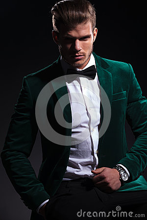 Man in elegant green velvet suit is sitting on a chair