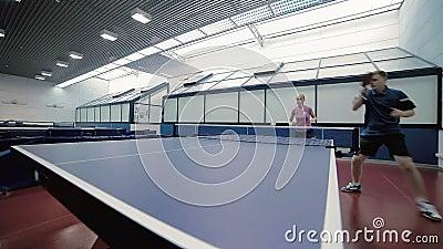 Man en vrouw die een pingpong spelen tegen de man stock footage