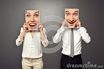 Man en vrouwenholding verbaasde gelukkige gezichten