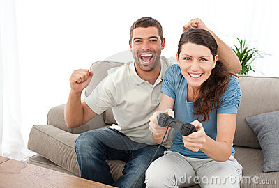 Man encouraging his girlfriend playing video game