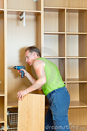 The man is engaged in repair and furniture