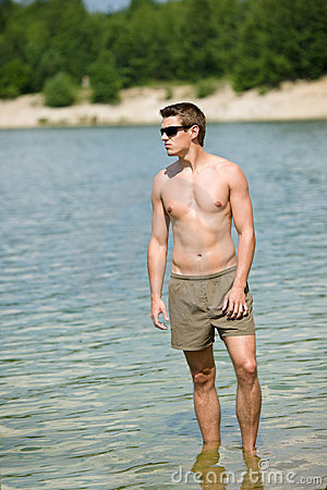 Man enjoy sun at seashore standing in water