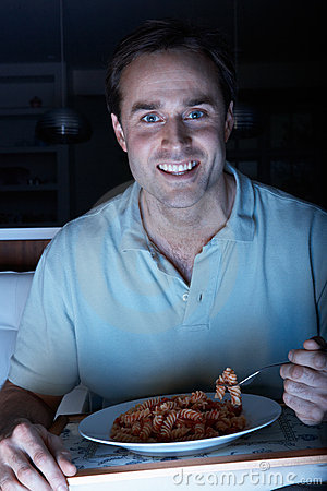 Man Enjoying Meal Whilst Watching TV