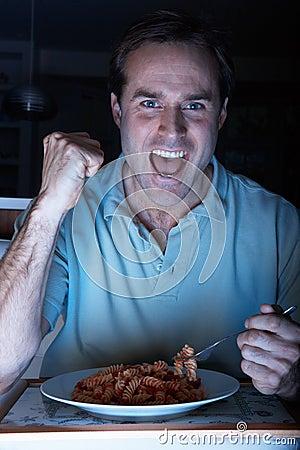 Man Enjoying Meal Whilst Watching TV