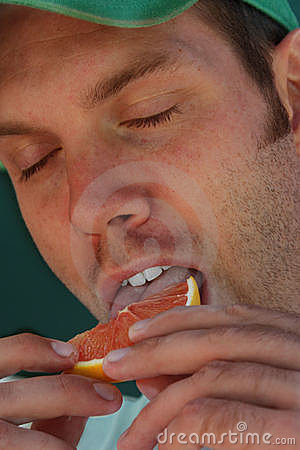 Man enjoying an orange