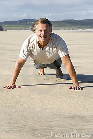 Man exercising on beach.