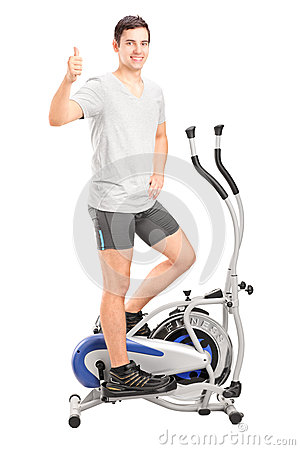 Man exercising on a cross trainer machine and giving thumb up