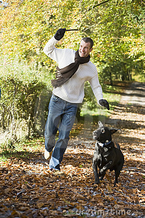 Man exercising dog in woodland